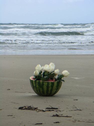 Beauty in the form of a bouquet in a watermelon on the beach.